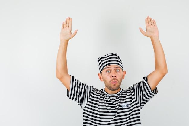 縞模様のtシャツ、帽子、怖い顔で降伏ジェスチャーで手を上げる若い男。