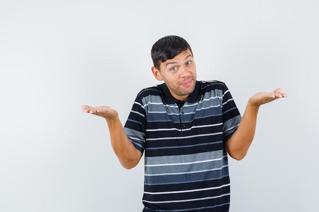 Молодой человек поднимает руки, как держит или показывает что-то в футболке и выглядит веселым, вид спереди.