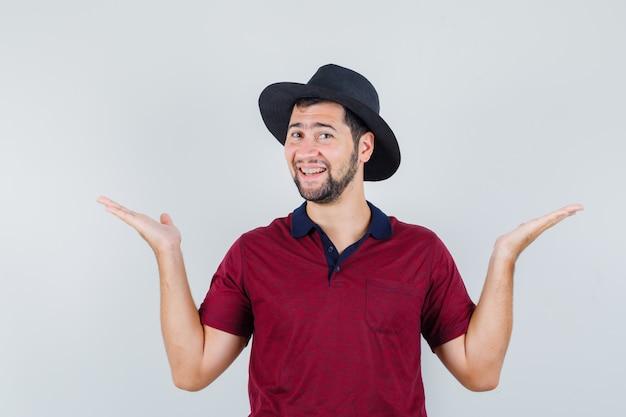 Tシャツ、帽子で何かを持ったり見せたりするように手を上げて、うれしそうに見える若い男。正面図。