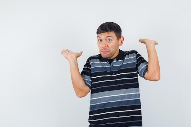 Молодой человек поднимает руки, как держит что-то в футболке и выглядит нерешительно, вид спереди.