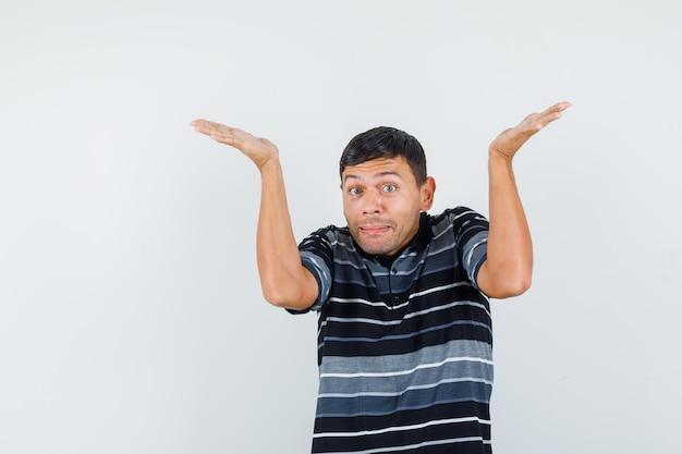 Молодой человек поднимает руки, как держит что-то в футболке, вид спереди.