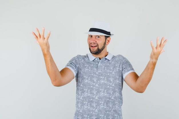 Giovane che alza le mani nel gesto interrogativo in maglietta bianca, cappello e guardando stupito, vista frontale