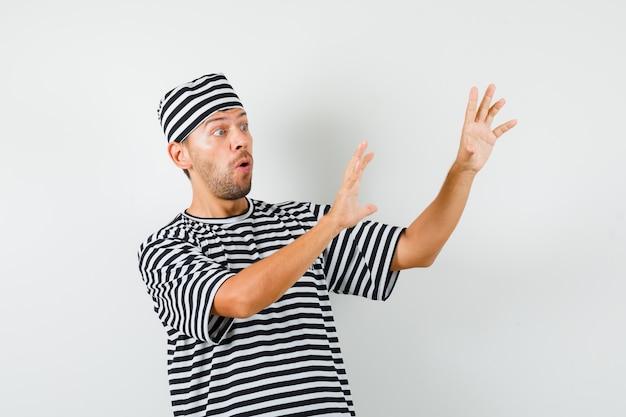 Молодой человек поднимает руки, чтобы защитить себя в полосатой футболке, шляпе и выглядит испуганным.