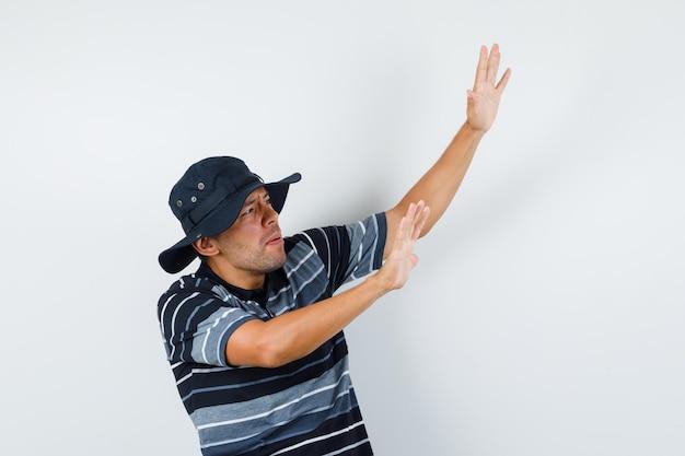 Молодой человек поднимает руки, чтобы защитить себя в футболке, шляпе и выглядит испуганным, вид спереди.