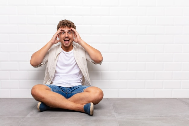 Молодой человек поднимает руки к голове, с открытым ртом