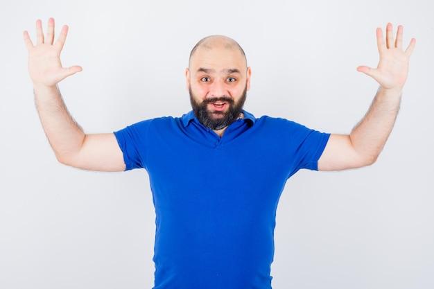 Giovane che alza le mani in camicia blu e sembra felice, vista frontale.