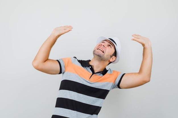 스트라이프 티셔츠, 모자와 무서워 보이는 방어를 위해 손을 올리는 젊은 남자. 전면보기.