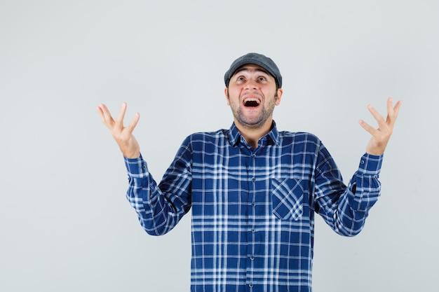 Giovane che alza le mani mentre cerca in camicia, berretto e sembra grato. vista frontale.