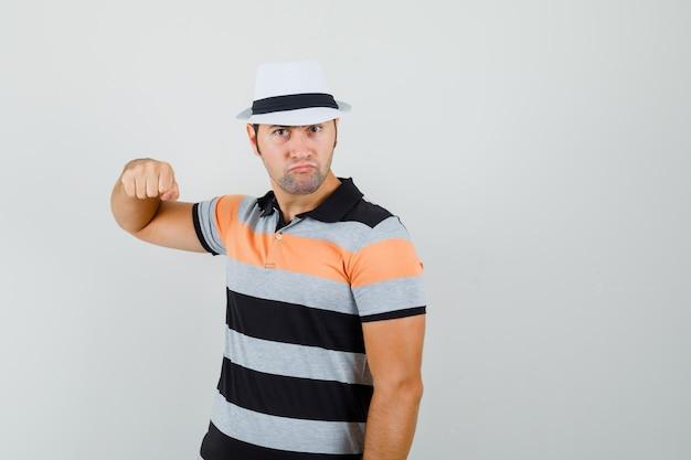 縞模様のtシャツ、帽子、怒っているように見える、正面図で彼の拳を上げる若い男。 無料写真