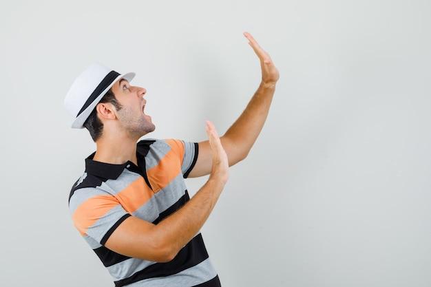 줄무늬 티셔츠, 모자에서 방어하기 위해 그의 열린 손바닥을 올리는 젊은이. 전면보기.