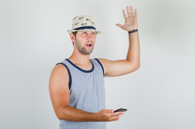 Молодой человек поднимает руку со смартфоном в серой майке, шляпе и выглядит удивленным