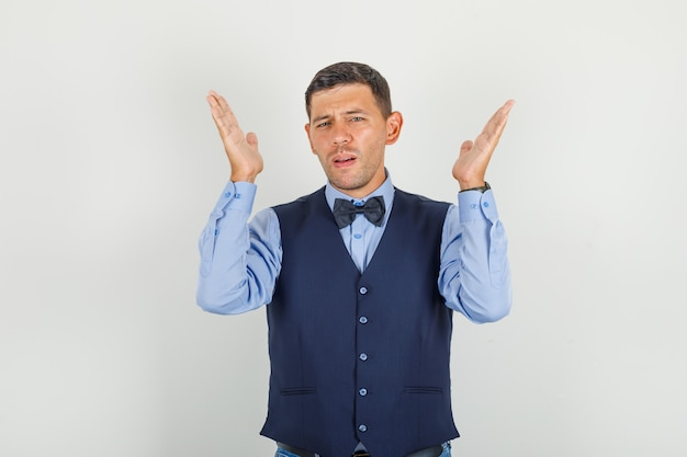 Young man raising open hands in suit, jeans and looking exhausted