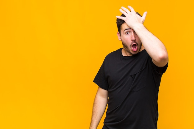 Young man raising palm to forehead thinking oops, after making a stupid mistake or remembering, feeling dumb