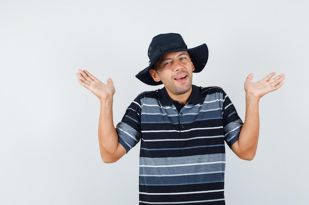 Молодой человек поднимает ладони в футболке, шляпе и выглядит любимым. передний план. Бесплатные Фотографии