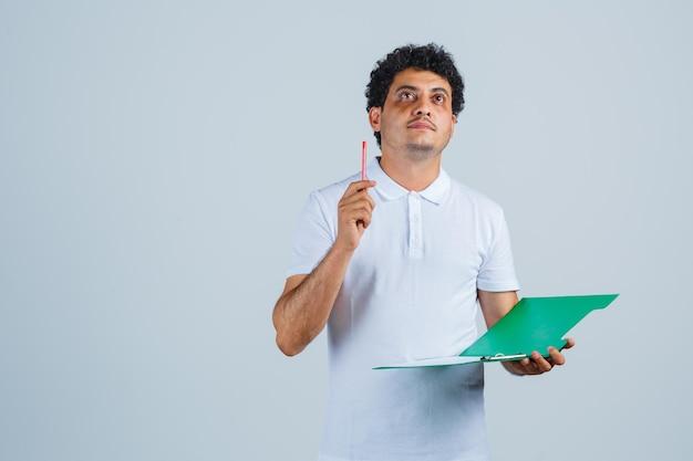 Giovane che alza la penna nel gesto di eureka e tiene il taccuino in maglietta bianca e jeans e sembra pensieroso. vista frontale.