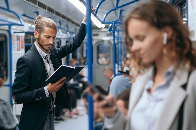 地下鉄の電車で本を読んでいる若い男