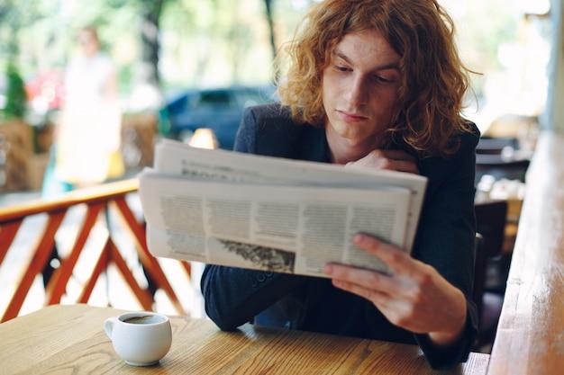 若い男が新聞を読む
