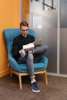 肘掛け椅子で厚い本を読んでいる若い男の人