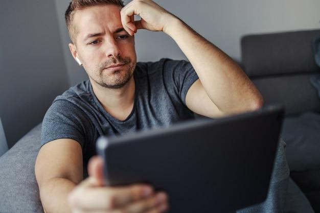 インターネットで悪いニュースを読んでいる若い男