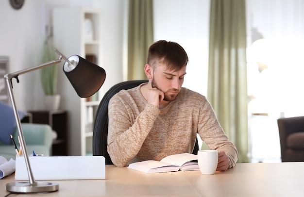 Молодой человек читает книгу дома