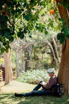 若い男が夏の芝生で本を読んで