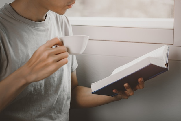 Young man reading book and drinking tea at living room in free time from working at home, knowledge and learning concept