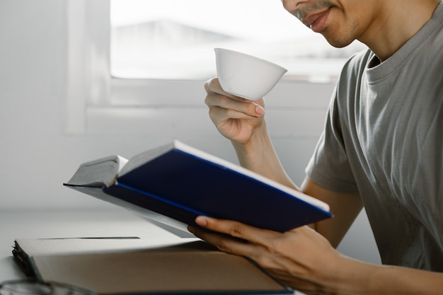Young man reading book and drinking tea at work desk in free time from working at home, knowledge and learning concept