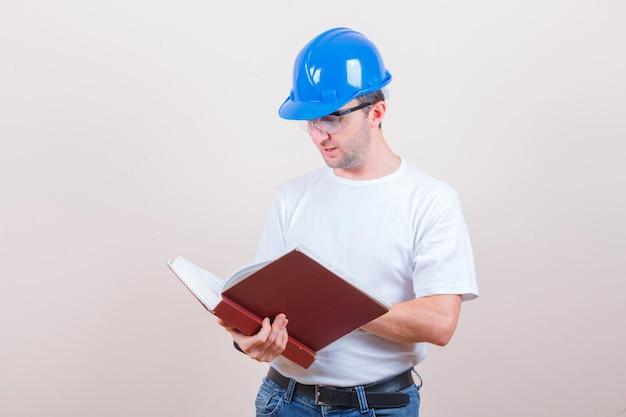 젊은 남자 티셔츠, 청바지, 헬멧에 책을 읽고 바쁜 찾고