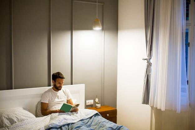 침대에서 젊은 남자 읽기 책