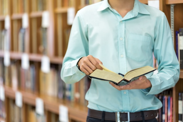 Young man reading book in library.