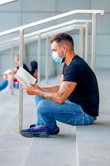 Молодой человек читает книгу на ступеньках университетского городка