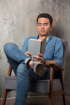 Young man reading a book and sitting on chair . high quality photo