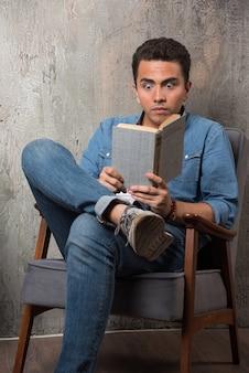 Giovane che legge un libro e che si siede sulla sedia. foto di alta qualità Foto Gratuite