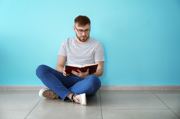 컬러 벽 근처에 앉아있는 동안 책을 읽는 젊은 남자