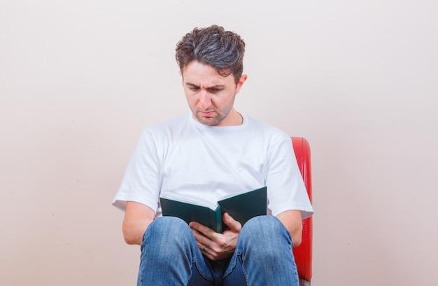 T- 셔츠, 청바지에 의자에 앉아 의아해 찾고있는 동안 젊은 남자가 책을 읽고