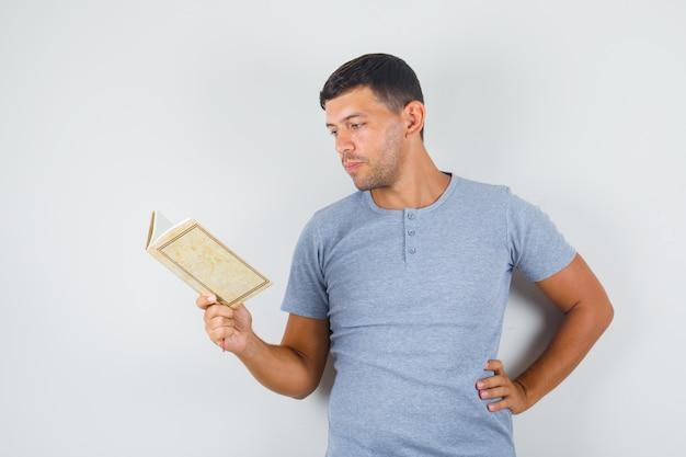若い男が灰色のtシャツで腰に手で本を読んで、注意深く探しています。