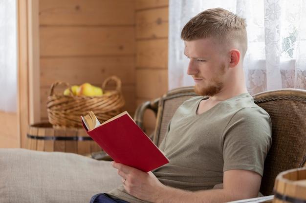 田舎の木造住宅の籐のベンチに赤いカバーで本を読んで若い男