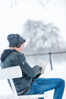 Young man reading and listening music in a snowy day.