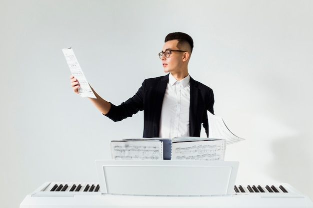 Young man reading the musical sheet standing behind the piano against white background