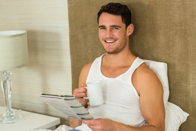 Young man reading newspaper while holding a cup of tea in bedroom