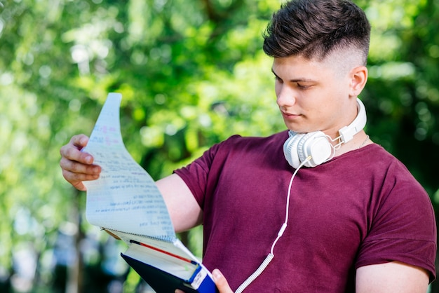 Young man reading notebook in park