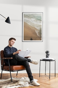 Young man reading a report in a cozy reading room while working from home