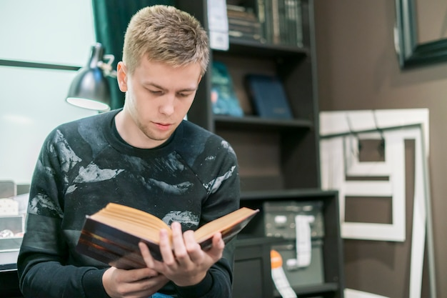Young man reading a science book in the workshop place