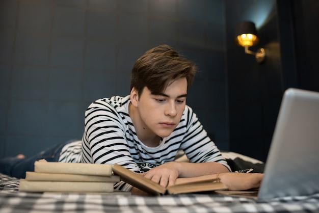 Молодой человек читает стопку книг, лежа на кровати