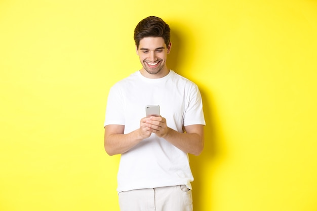 Молодой человек читает текстовое сообщение на смартфоне, смотрит на экран мобильного телефона и улыбается, стоя в белой футболке на желтом фоне
