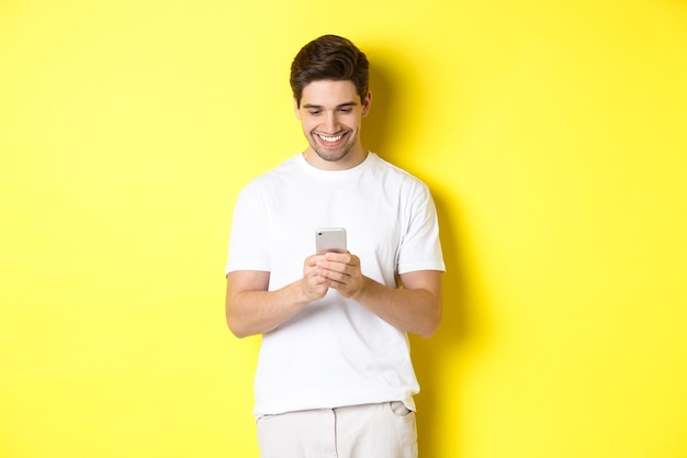 Young man reading text message on smartphone, looking at mobile phone screen and smiling, standing