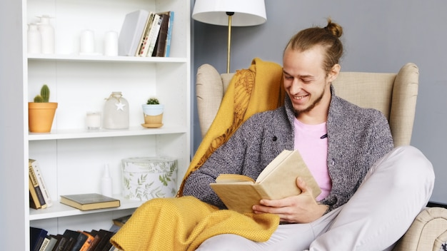 A young man reads a book in a cozy interior.