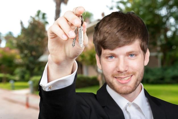 若い男の全米リアルター協会加入者またはセールスマネージャー、車または家の鍵を表示