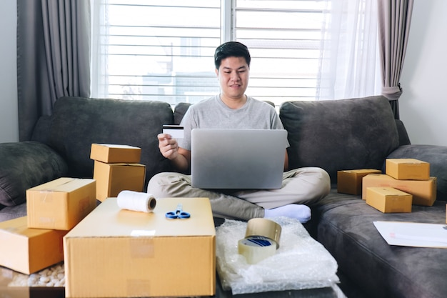 Young man received online shopping parcel opening boxes and buying items by credit card, online marketing on purchase order