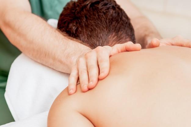 Молодой человек получает массаж спины в салоне красоты спа.